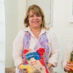 Roberta sorri para a foto, segurando um saco de arroz