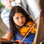 Thainá toca violino concentrada, olhando para a frente